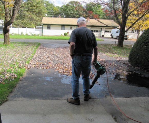 A man uses an electric leaf blower.