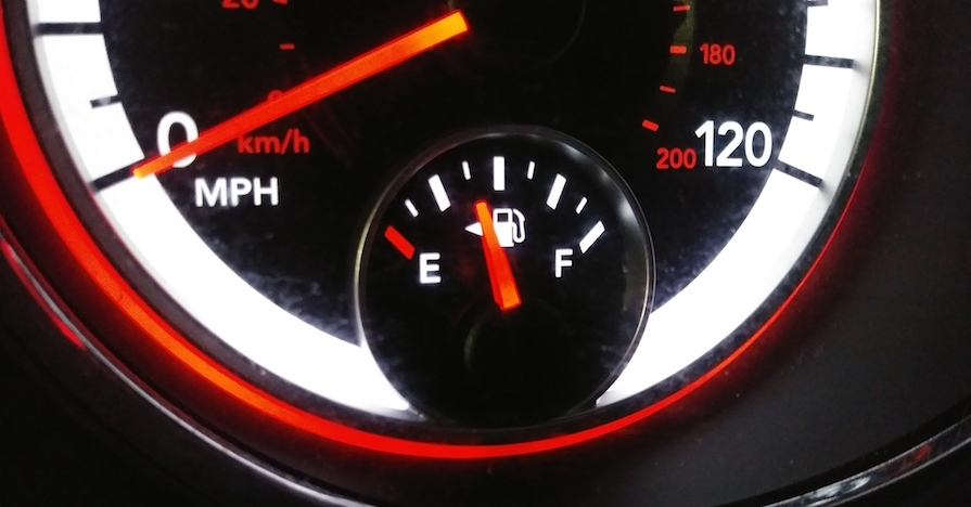 A car dashboard shows an odometer and fuel measurements. Driving with the gas light on can cause damage.