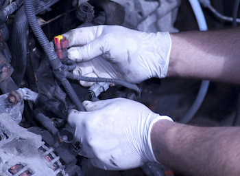 A man works on installing a new engine.