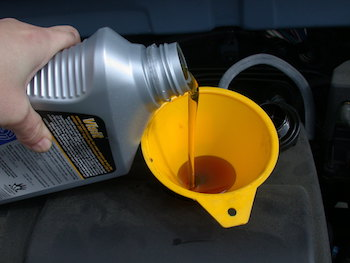 Motor oil being poured into an engine using a yellow funnel.