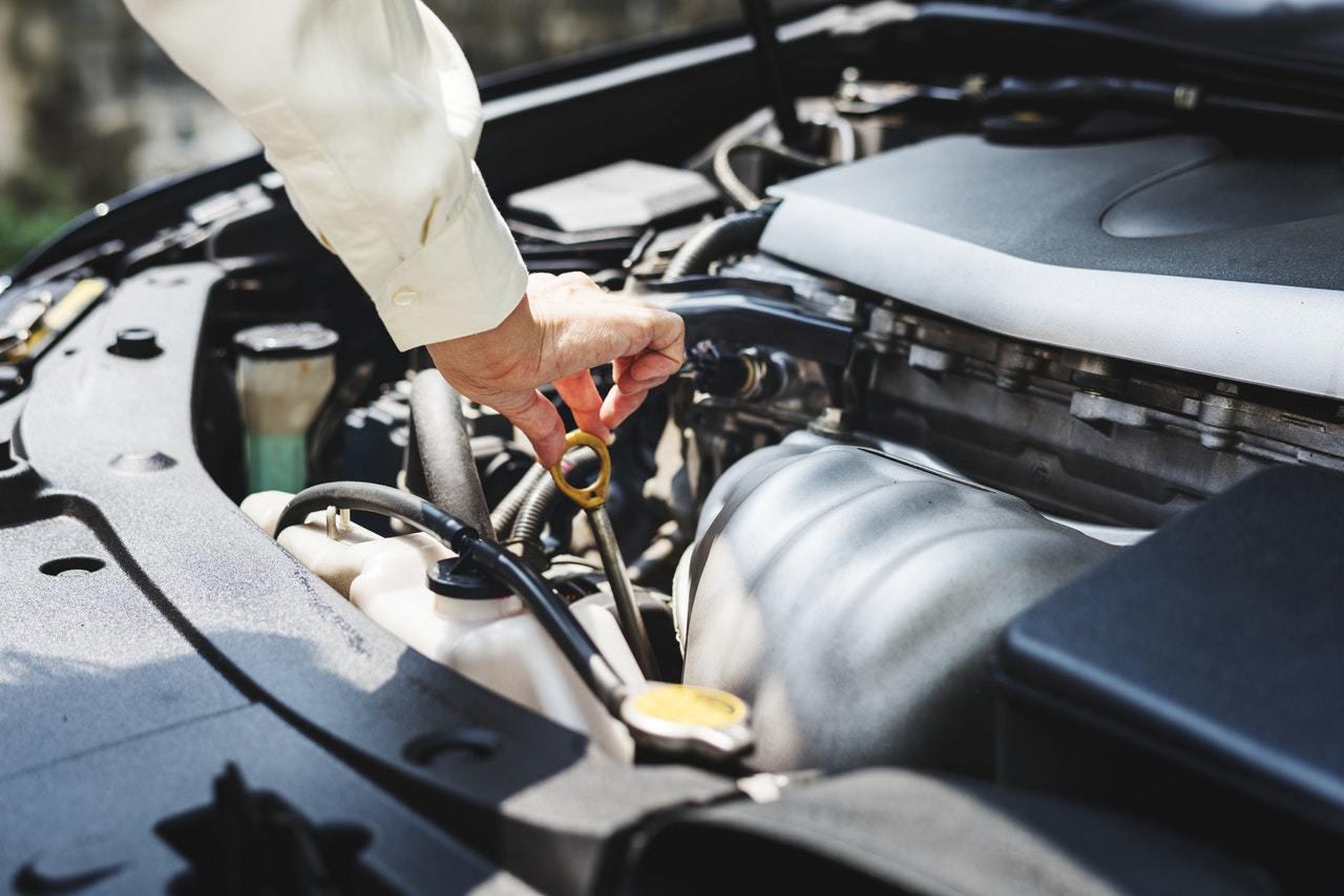 A man checking his car's oil.