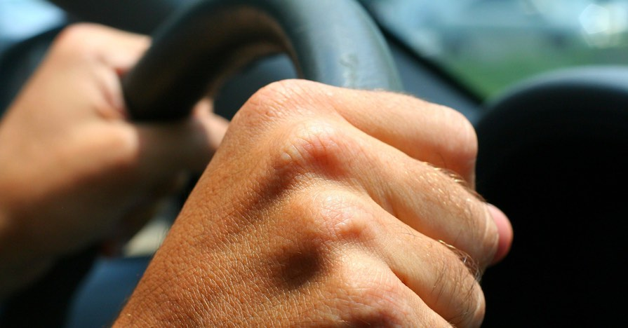 A man holds a steering wheel.