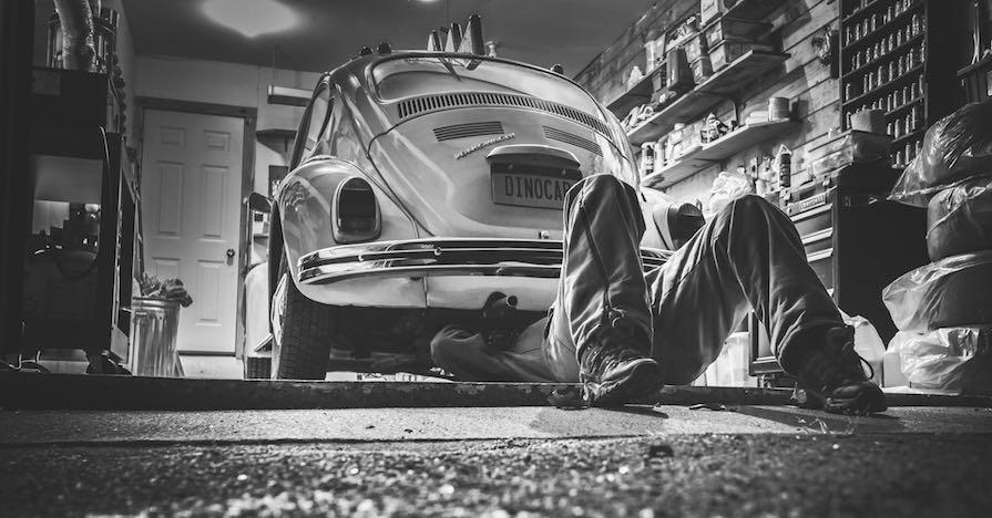 A man repairing a classic Volkswagen.