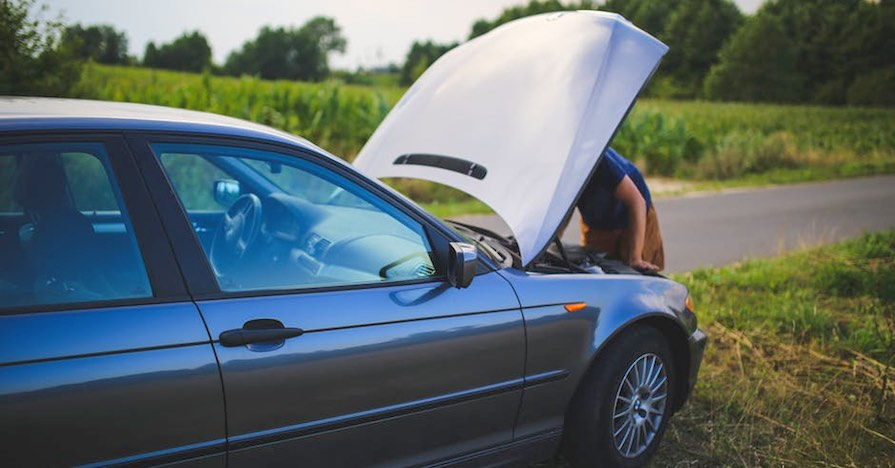 A driver looking at the car's engine bay. An overheating engine can be a major issue for a vehicle. Here's what you should do if you suspect that your engine running hot