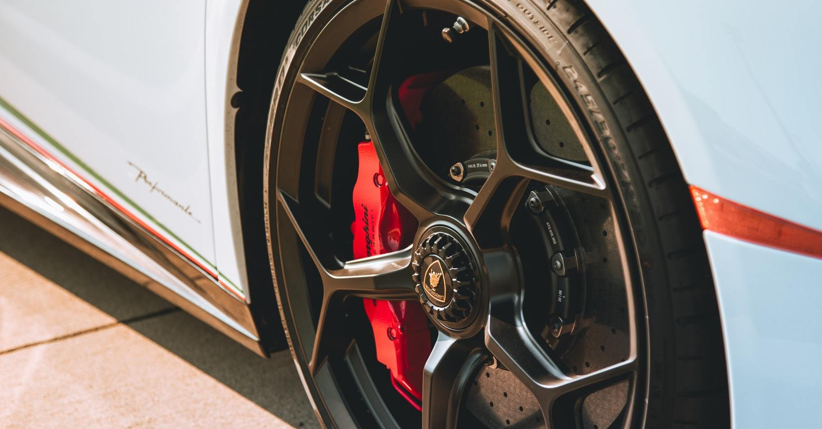 Disc brakes on a Lamborghini. Modern vehicles use disc and drum brakes. Here are the differences between the two, including the pros and cons of each respective system.