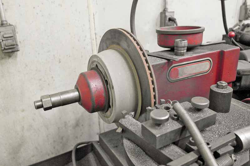 The lathe spins the rotor and a pair of cutters slowly remove the damaged metal.