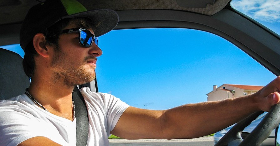 A man driving on a summer day. There are five major things to check when preparing your car for summer. From checking your car's tires to checking the air conditioning system, here's what you should do if you're getting ready for summer.