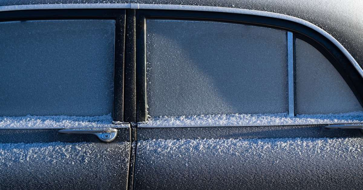 Frost and snow on the windows and doors of a car