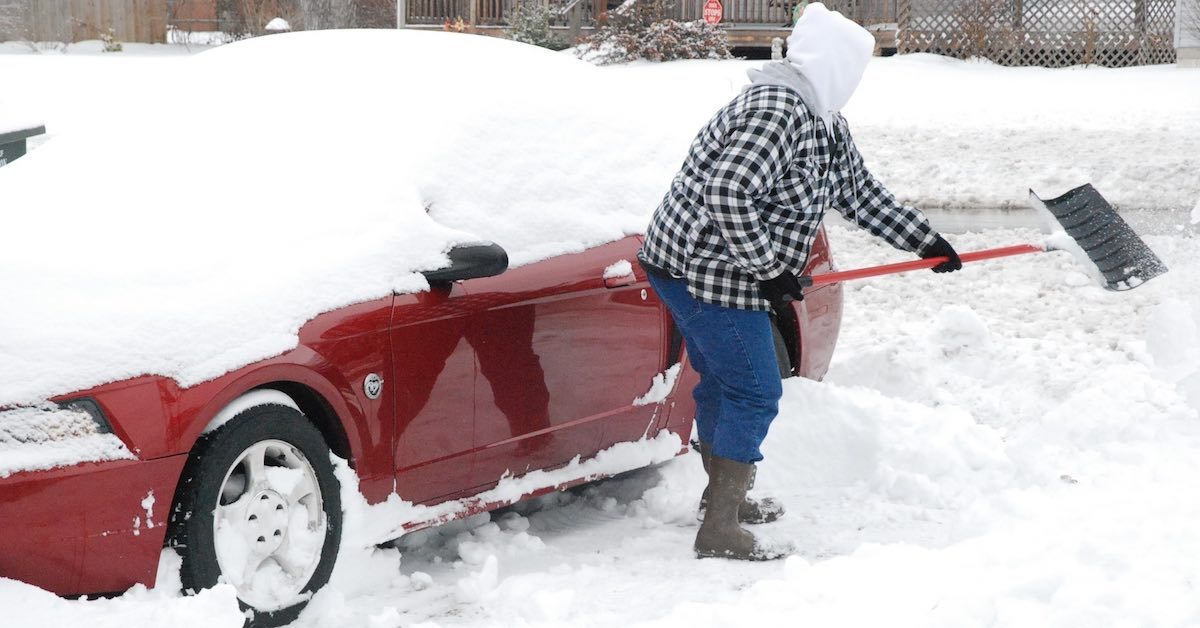 A person in a checkered coat shoveling snow next to a snow-covered red car