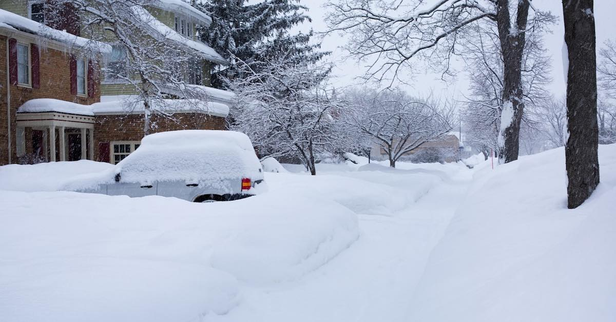 A car parked in a driveway in front of a house covered in snow