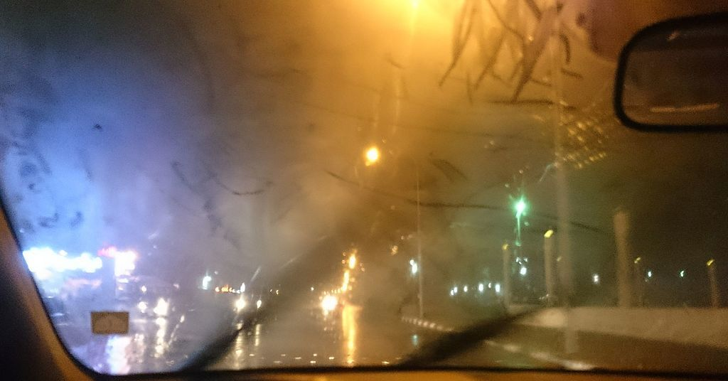 Looking through a foggy windshield onto a street at night