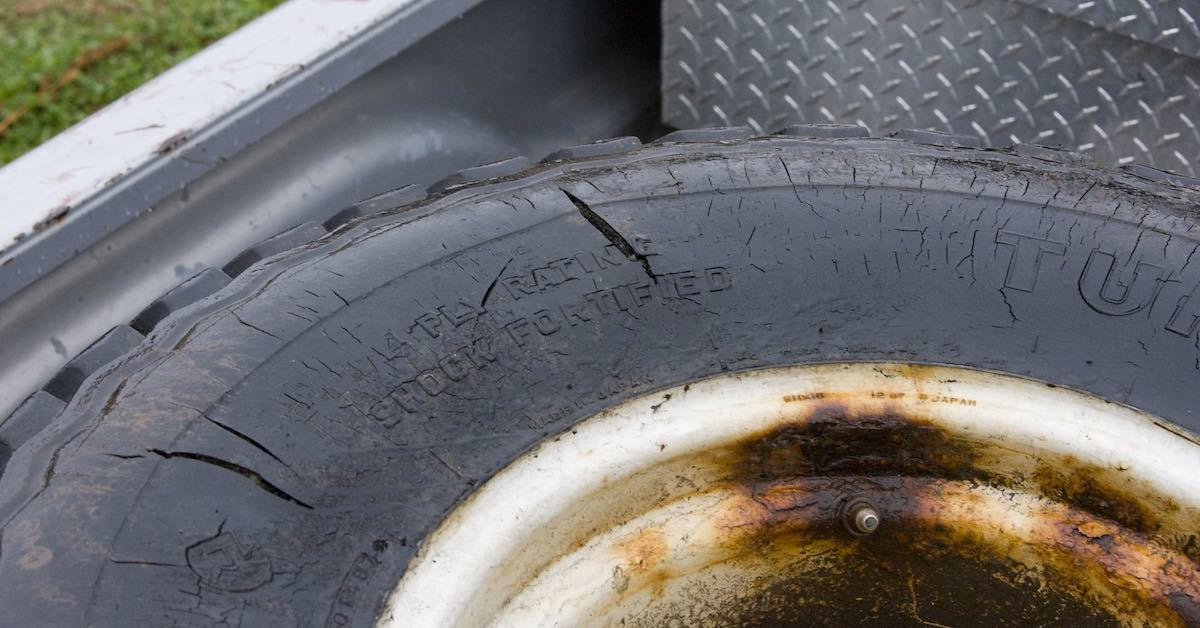 Tire with significant damage to the sidewall and a rusty rim