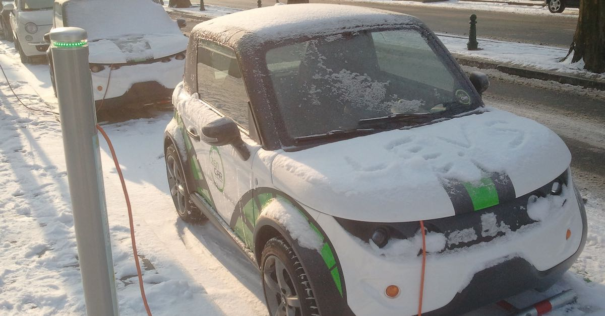 An electric car charging on a snowy road
