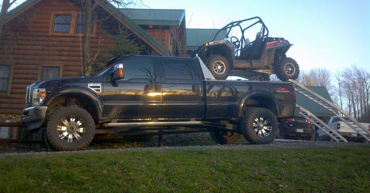 A pickup truck with metal ramps sticking out the back and a UTV loaded into the bed in front of a house
