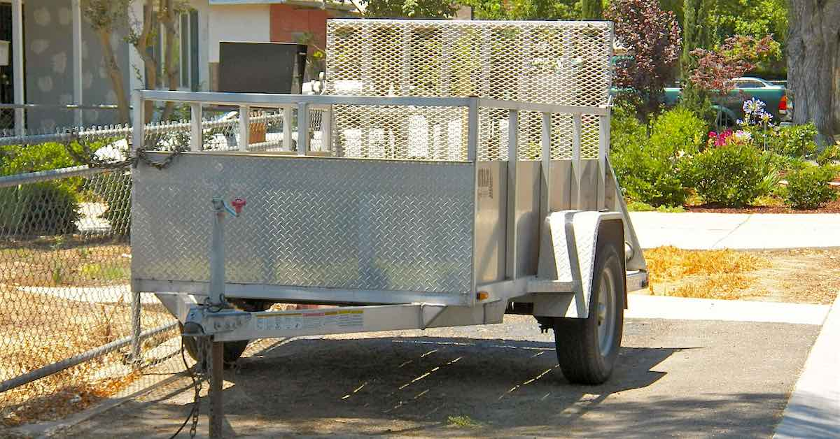 White utility trailer parked beside a house