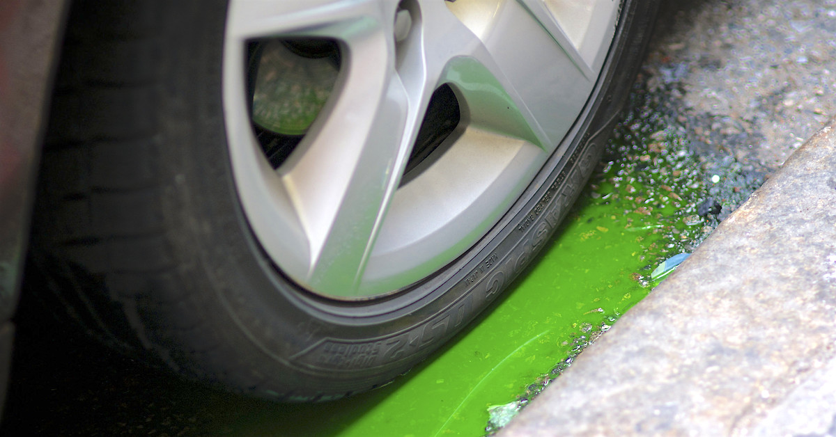 Green fluid puddled around car tire