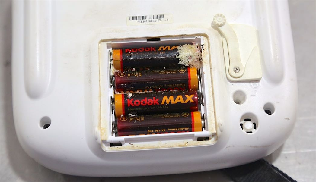 This remote control for an aerial drone was left with the batteries in place for well over a year. They leaked and now we have a mess.