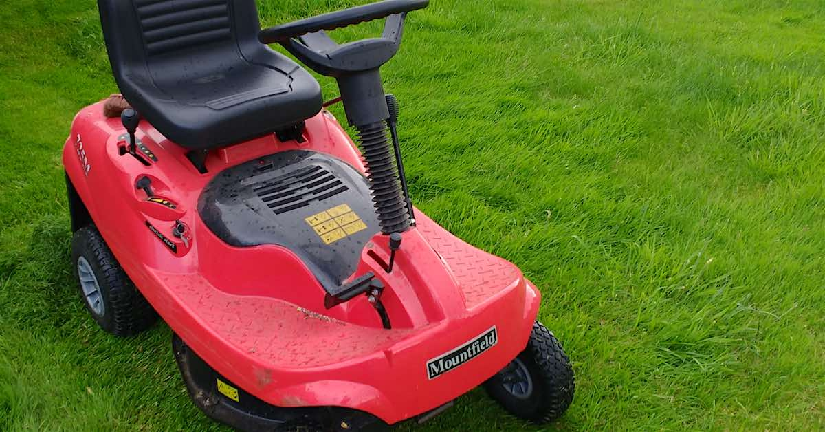 Red riding lawn mower on lush green grass