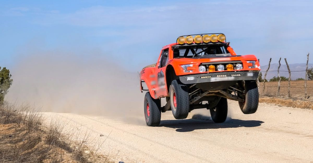 A red truck doing a jump on a dirt road