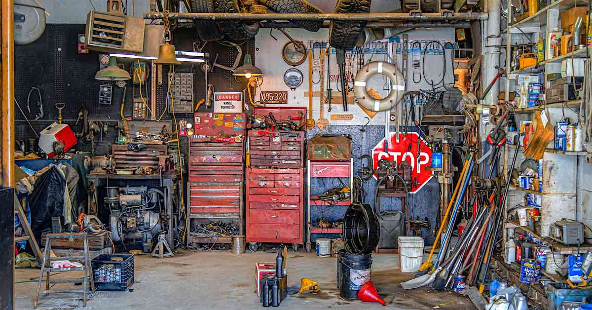 A cluttered garage with tools, extra tires and more