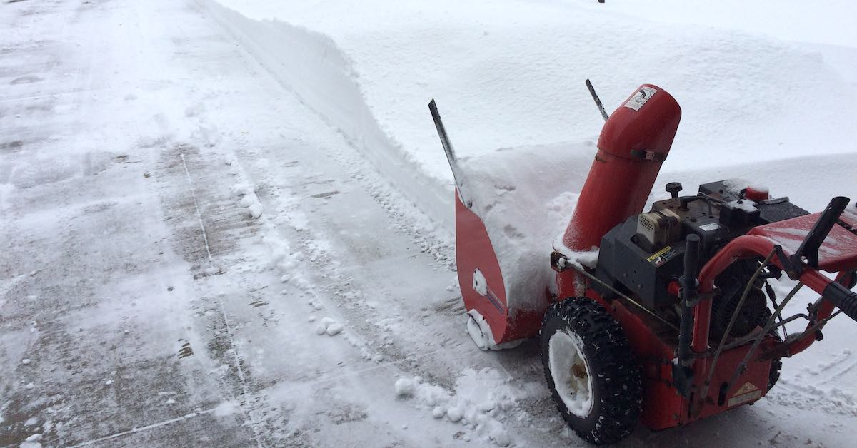 A snowblower on a snowy street.