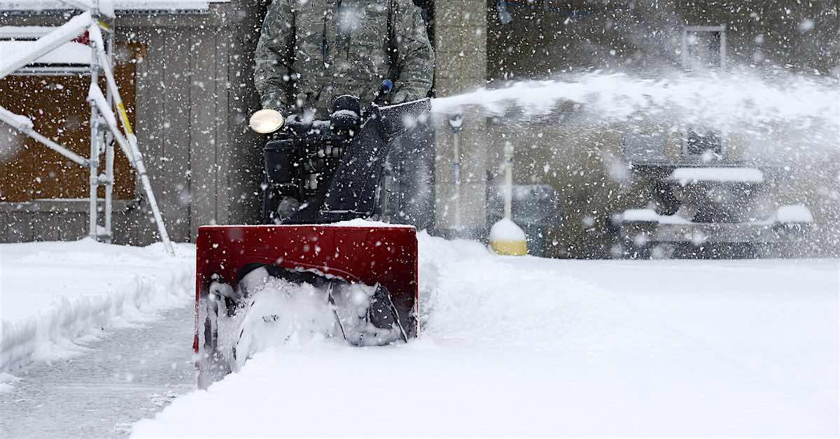 A person snowblows a driveway.