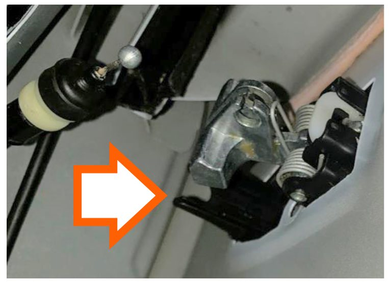 With the handle held in place, reach through the interior side of the door, place the repair bracket over the handle, and align it with the mounting bolts.
