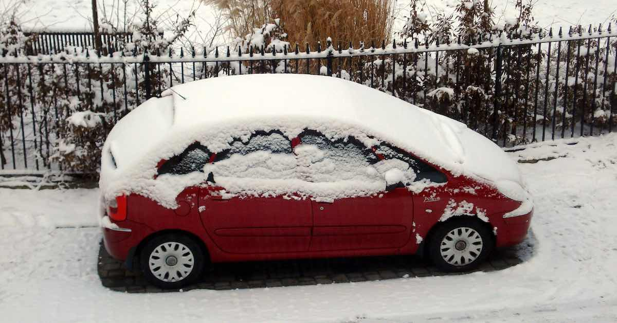 An iced-over car parked on a city street.
