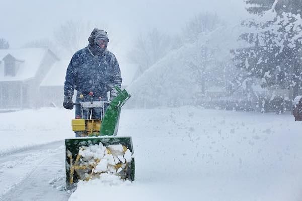 man using snow blower during snowfall