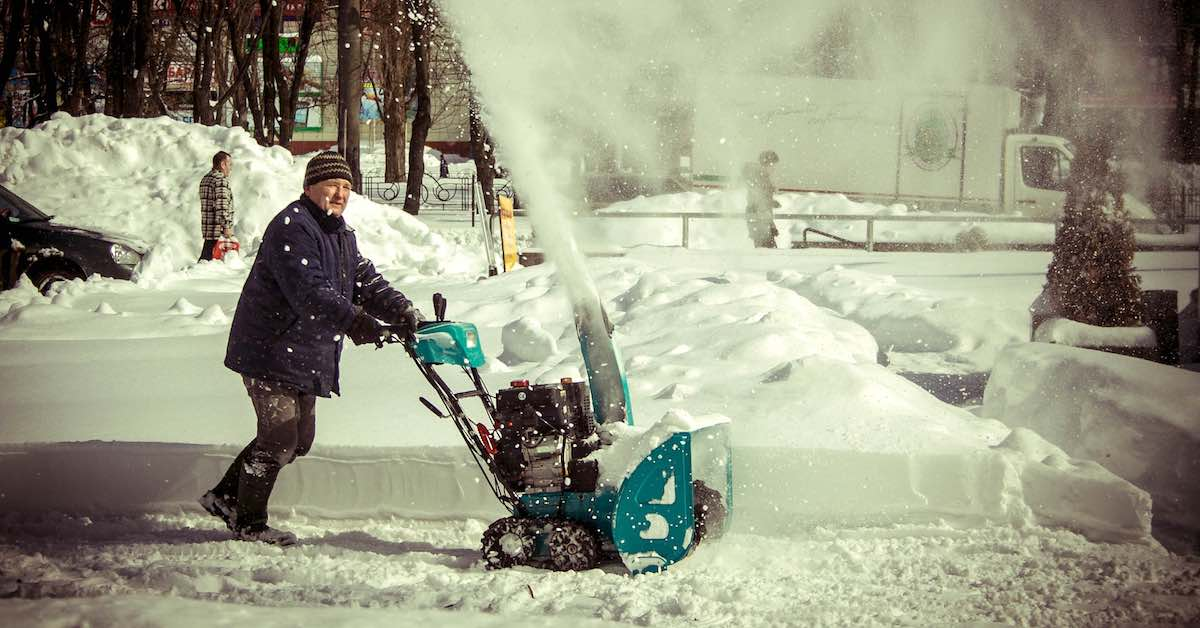 A man uses a snow blower on his driveway.