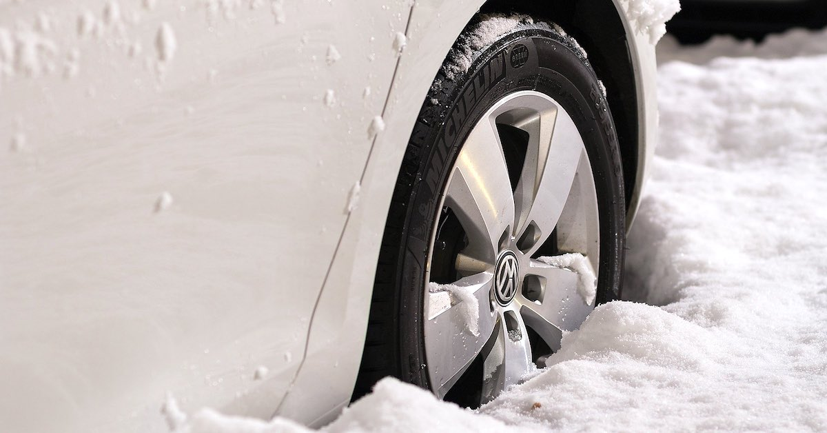 A car with snow tires navigates deep snow.