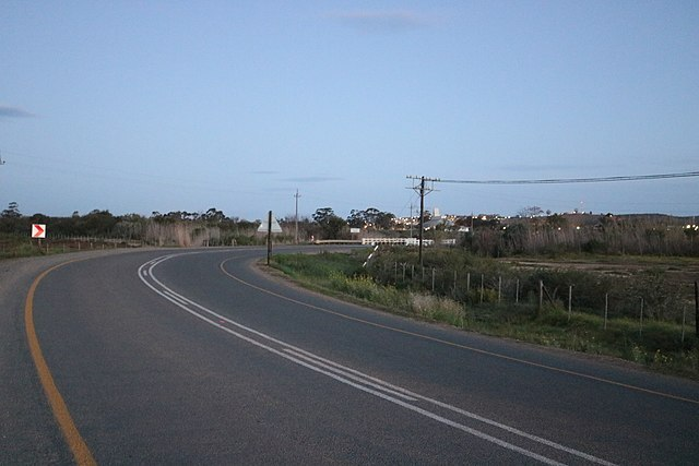 Tar road curving to the right and then white bridge