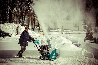 A man uses a snow blower to clear away the snow following a storm.