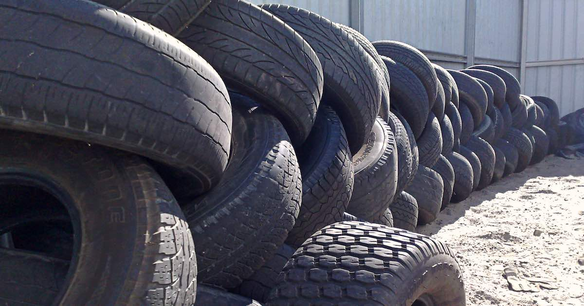 Many old tires stacked up awaiting recycling.