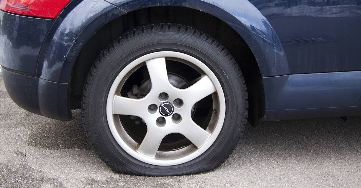 A car with a tire that has suffered a blowout.