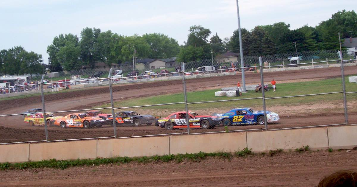 Full-body stock cars race around a dirt track.