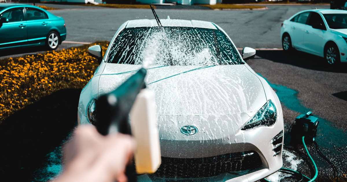 A white car being washed with a foam cannon.