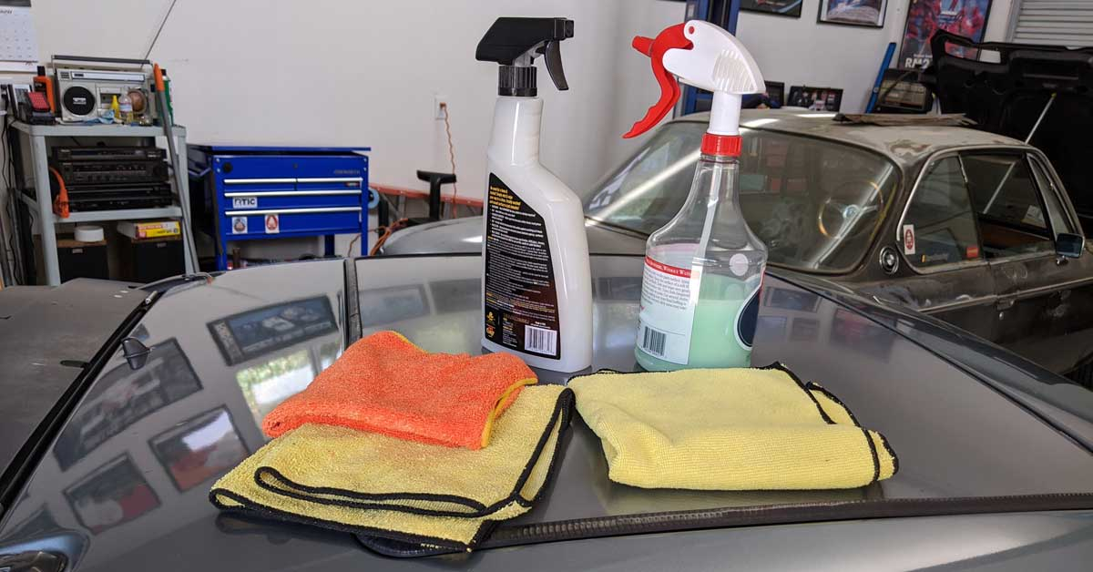 Cleaning supplies on the roof of a car in a garage.