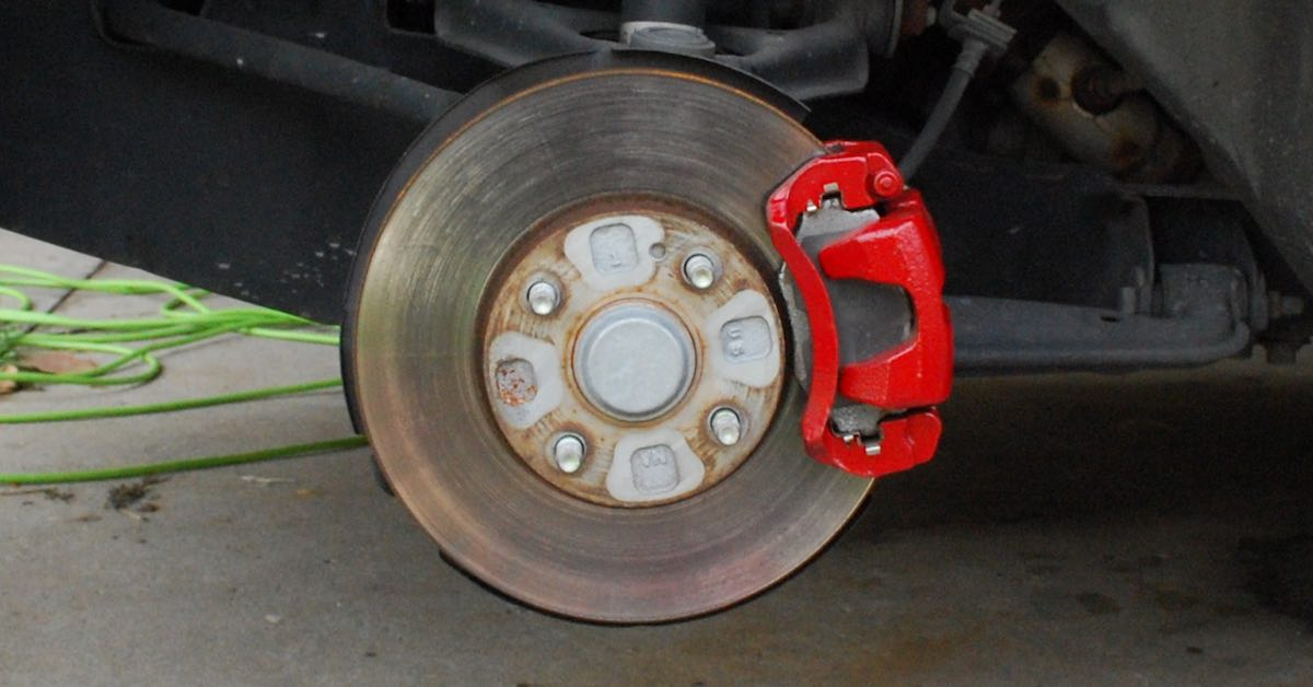 A brake caliper of a car as seen with the wheel removed.