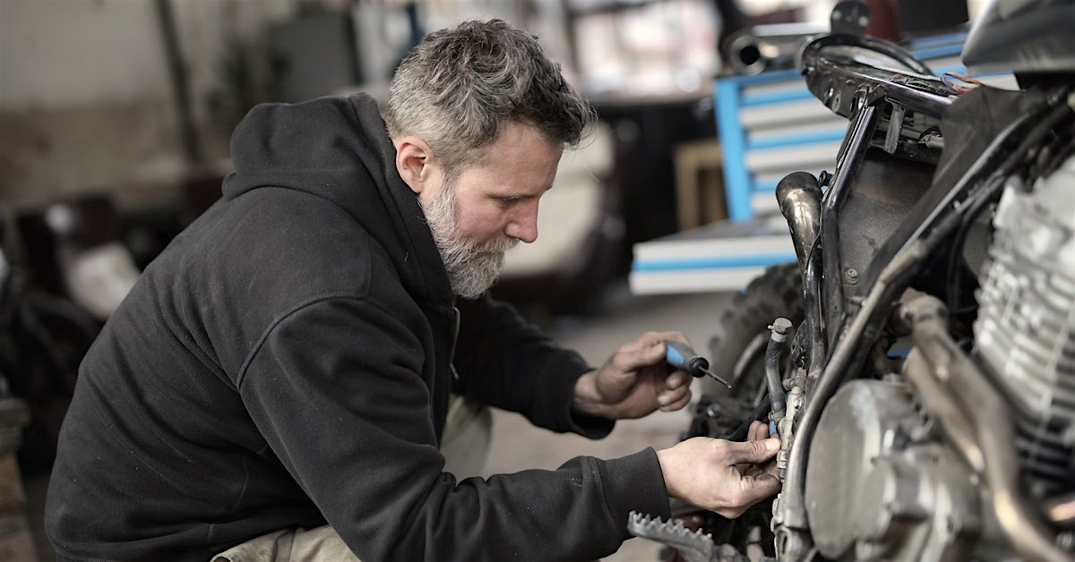 A man works on his motorcycle.