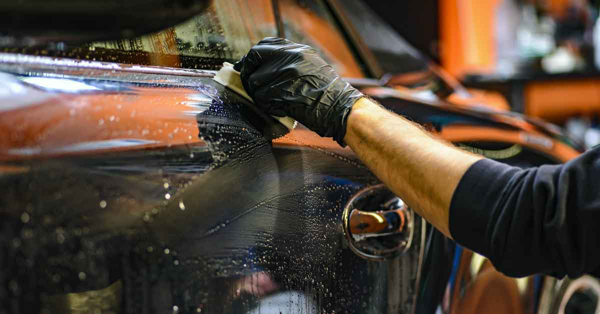 A gloved hand cleaning a car.