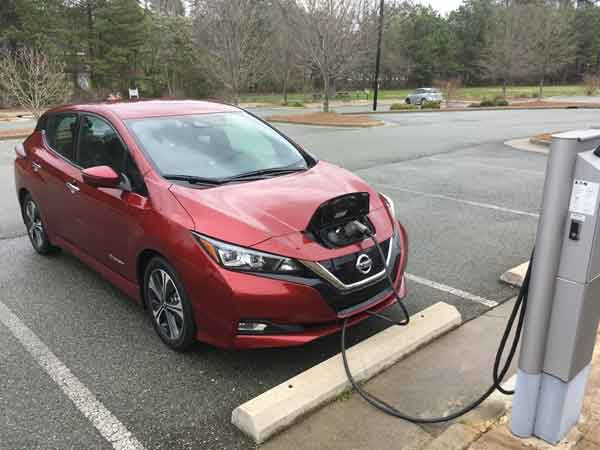 A Nissan Leaf connected to a public charging station.
