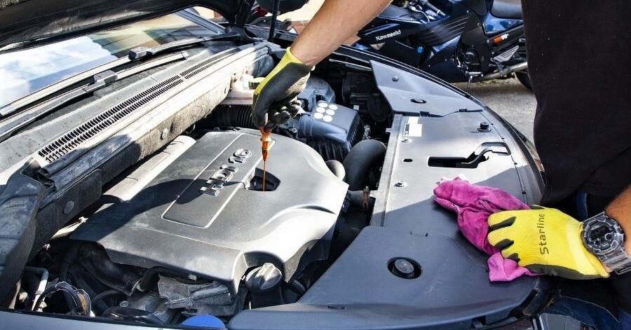 A mechanic checks the oil in an Audi.