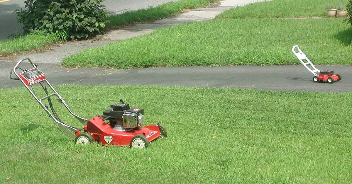 A lawn mower and a toy lawn mower.