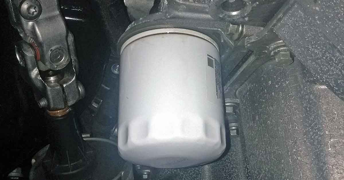 A white oil filter installed in the engine bay of a car