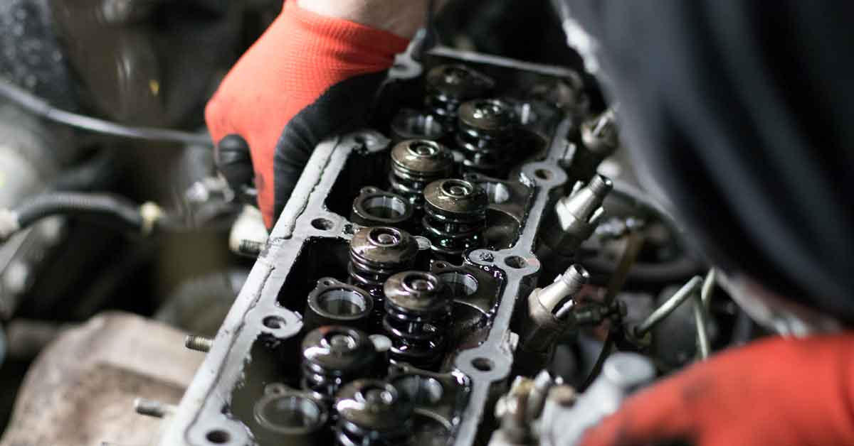 A mechanic removes cylinder heads from a car.