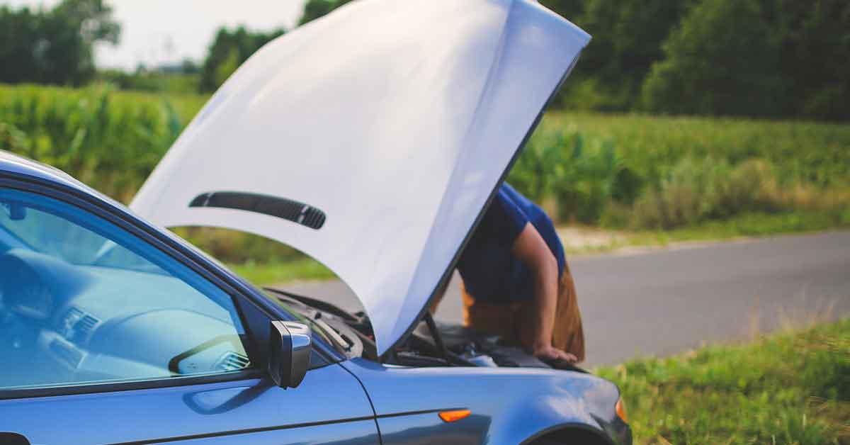 A man peers under the hood of his car.