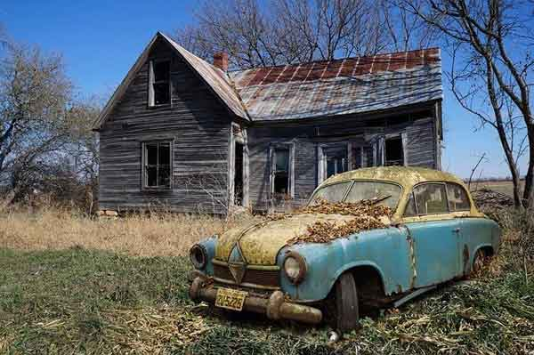 A rusty car by a dilapidated shack.